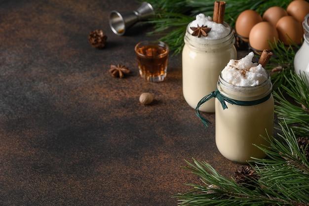 暗い背景にスパイスとアルコールとメイソンジャーの休日のクリスマスエッグノッグ。閉じる。