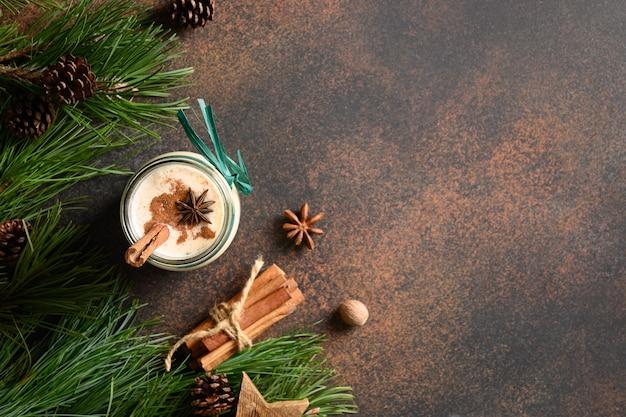 茶色の背景にシナモンとアニスの星とホリデークリスマスエッグノッグ上面図コピースペース