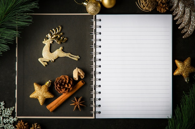 Holiday christmas frame card and vintage blank open book notes on the dark table