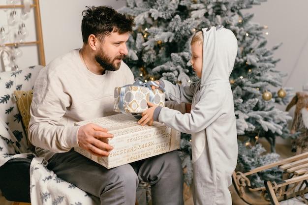 Праздник рождества красивый отец играет с маленьким симпатичным сыном возле украшенной новогодней елки дома семейная традиция мальчик делает подарок своему отцу