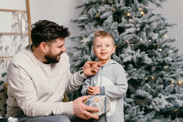 Holiday christmas handsome father playing with small cute son near decorated new year tree at home family tradition father gives a gift to his little boy