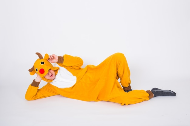 Holiday, christmas and people concept - man in santa claus deer costume lying on the white floor