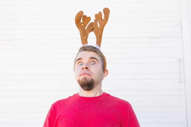 Holiday, christmas and people concept - surprised man in christmas costume over white background.