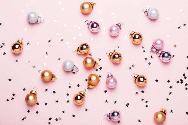 Праздник рождества розовый плоский лежал с золотыми блестящими шарами и конфетти.