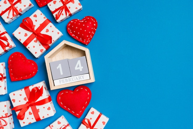 Holiday composition of gift boxes, wooden calendar and red textile hearts on colorful background with empty space for your design. the fourteenth of february. top view of valentine's day concept