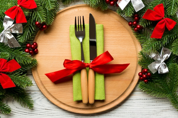 Holiday composition of plate and flatware decorated with fir tree on wooden surface.