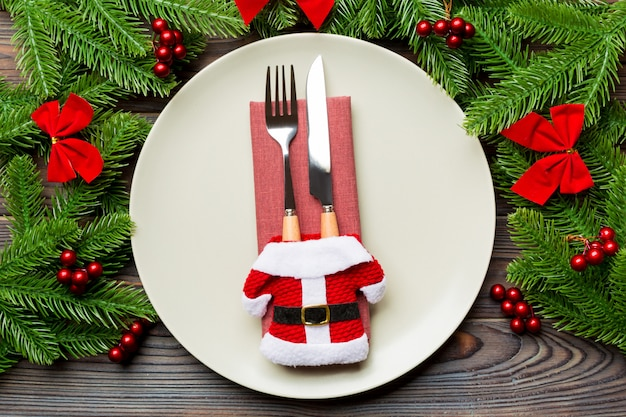 Holiday composition of plate and flatware decorated with santa clothes on wooden surface