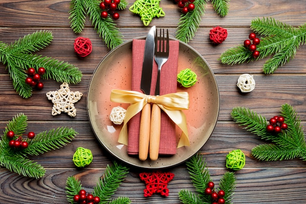 Holiday composition of plate and flatware decorated with santa hat on wooden background