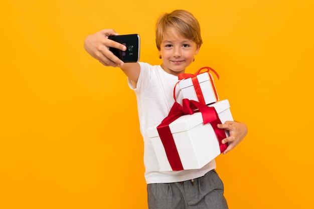 休日のコンセプトです。赤いリボンが付いているギフト用の箱を持つ魅力的な少年は明るい黄色の電話でselfieを取る