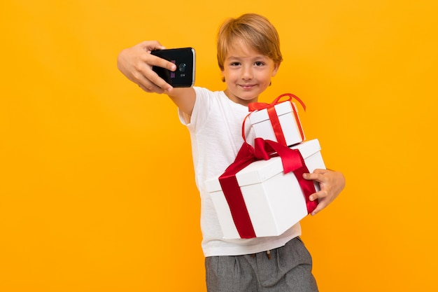 Holiday concept. attractive boy with a gift box with a red ribbon takes a selfie on the phone on bright yellow