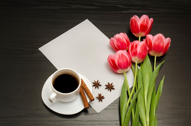Holiday concept. bouquet of pink tulips, a cup of coffee, cinnamon, star anise and sheet of paper on black wood