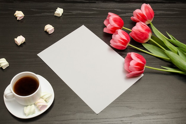 Holiday concept. bouquet of pink tulips, a cup of coffee, marshmallow and sheet of paper on a black wooden background