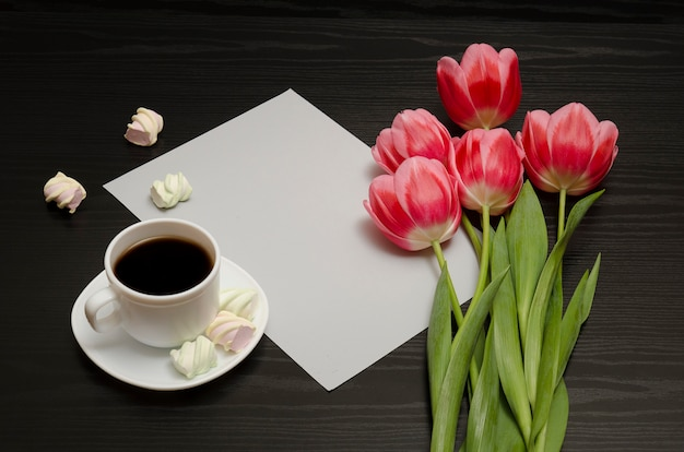 Holiday concept. bouquet of pink tulips, a cup of coffee, marshmallow and sheet of paper