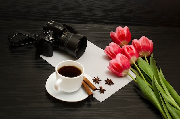 Holiday concept. bouquet of pink tulips, dslr camera, cup of coffee, cinnamon, star anise and sheet of paper