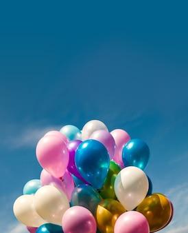 休日のコンセプト。空の背景にカラフルな風船の束