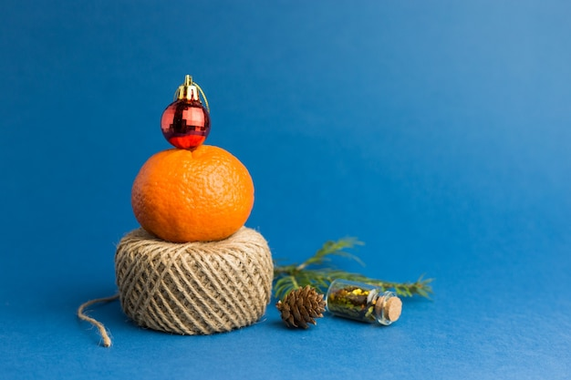 Holiday concept. christmas tree made of tangerine, christmas bauble and rope. color of the year, blue trendy background.