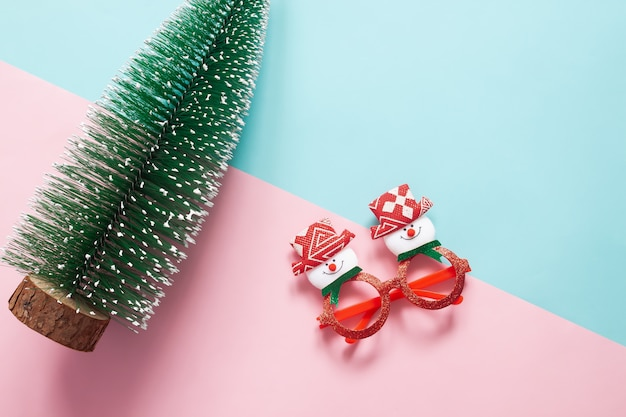 Holiday concept : flat lay of christmas ornaments and decorations on green and pink background