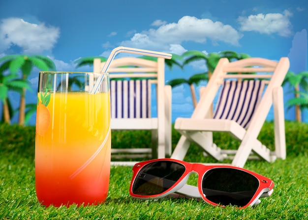 Holiday concept orange juice lounge chairs sunglasses on the grass