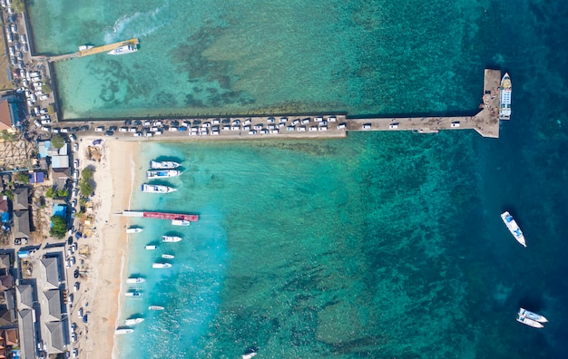 Holiday concept. top down drone shot of cars entering nusa penida island via toya pakeh harbour. bali - indonesia