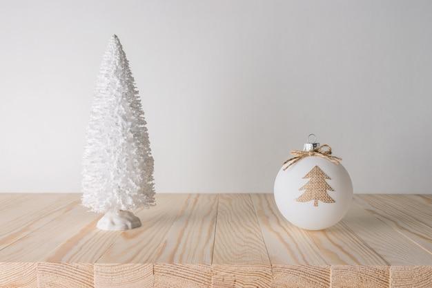 Концепция праздника с рождественской безделушкой и рождественской елкой на деревянном столе