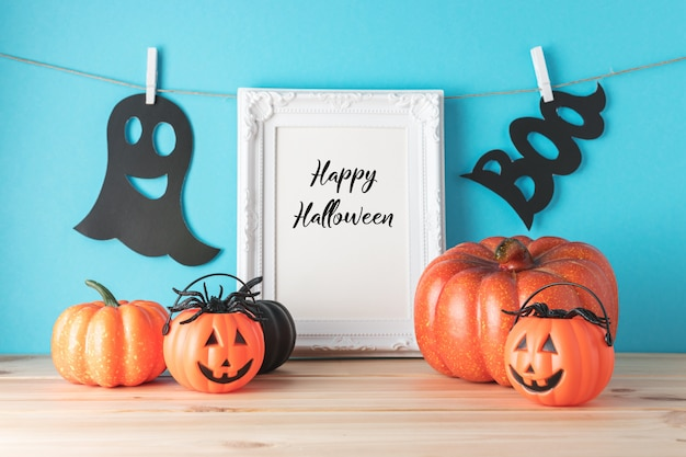Holiday concept with halloween pumpkin decor and photo frame on wooden table.