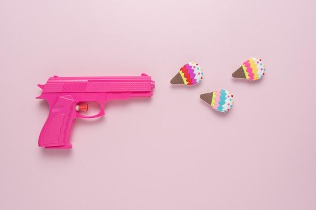 Концепция праздника с розовым пистолетом на розовом пастельном фоне с декором из мороженого