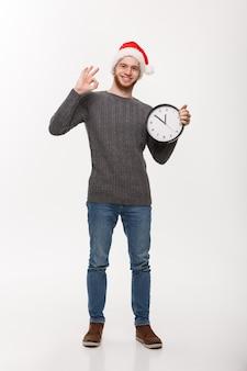 휴일 개념-확인 표시를주는 흰색 시계와 스웨터에 젊은 잘 생긴 수염 남자.