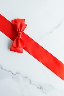 휴일 장식 여성스러운 디자인과 flatlay 개념 대리석 평면도에 빨간색 실크 리본