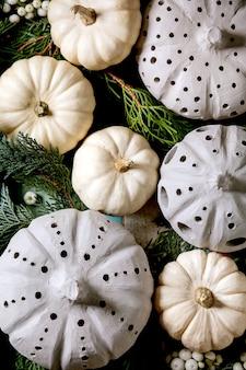 Украшение праздника с белыми декоративными тыквами, тыквами глины корабля, ветвями туи над старым деревянным фоном. плоская планировка, крупный план