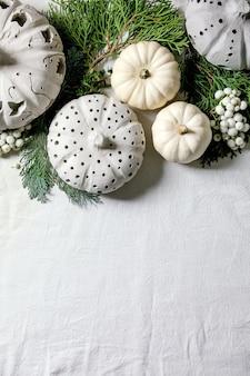 Праздничное оформление с белыми декоративными тыквами, глиняными тыквами, ветками туи над старым деревянным столом. плоская планировка, копия пространства