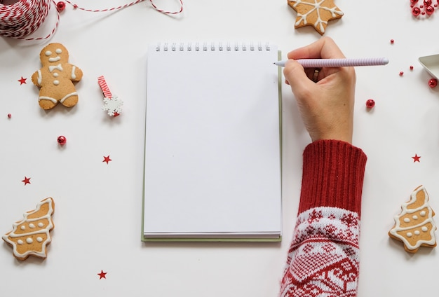 Holiday decorations and notebook with clean note book on white table, flat lay style.