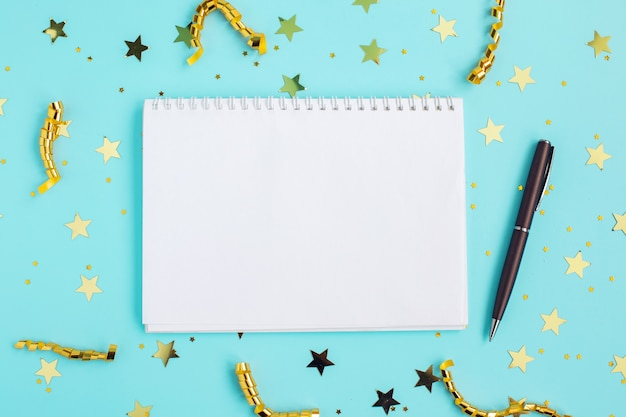 Holiday decorations and open notebook with gold confetti on blue background. change and determination concept.