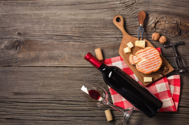 Holiday dinner setting with red wine and creaming cheese on rustic wood. top view with space for your greetings.