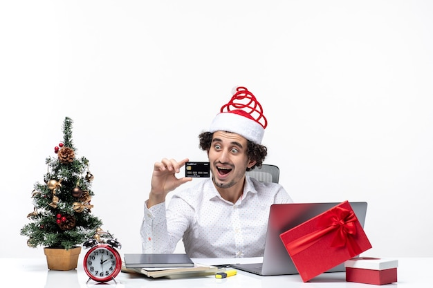Holiday festive mood with shocked business person with santa claus hat and looking at his bank card in the office on white background