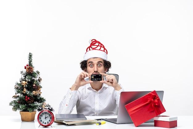 Праздничное праздничное настроение с удивленным деловым человеком в шляпе санта-клауса, показывающим банковскую карту и в офисе
