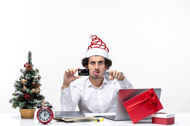サンタクロースの帽子をかぶって、彼の銀行カードを保持し、白い背景の上のオフィスで何かを指している若いビジネスパーソンとの休日のお祭り気分