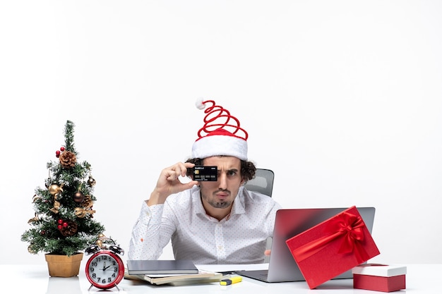 Holiday festive mood with young business person with santa claus hat and showing bank card and in the office on white background
