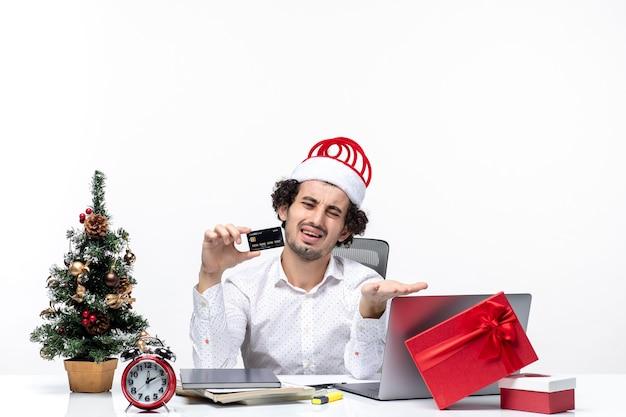 Umore festivo vacanza con giovane uomo d'affari arrabbiato stanco con cappello di babbo natale e tenendo la sua carta di credito in ufficio su sfondo bianco stock photo