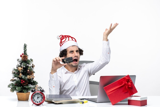 Holiday festive mood with young tired angry business person with santa claus hat and holding his bank card in the office on white background