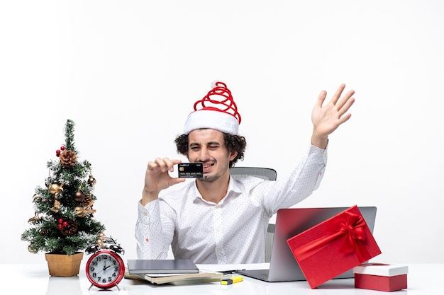 Holiday festive mood with young tired angry business person with santa claus hat and looking at his bank card in the office on white background