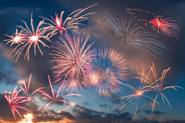 Holiday fireworks in the evening sky with majestic clouds Premium Photo