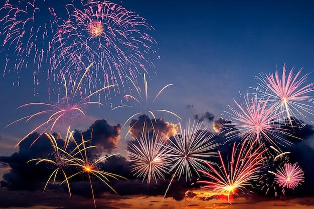 Праздничный фейерверк в вечернем небе с величественными облаками, длительная выдержка