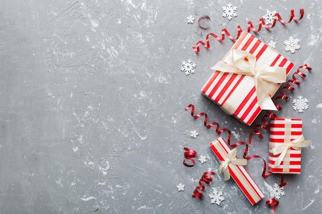 Праздничная квартира лежала с подарочными коробками, завернутыми в красочную бумагу и перевязанными, украшенными конфетти на цветном фоне. рождество, день рождения, валентинка и концепция продажи, вид сверху.