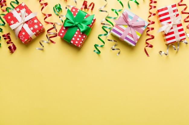 カラフルな紙で包まれ、色付きの背景に紙吹雪で飾られて結ばれたギフトボックスで休日のフラットレイ。クリスマス、誕生日、バレンタイン、セールのコンセプト、上面図。