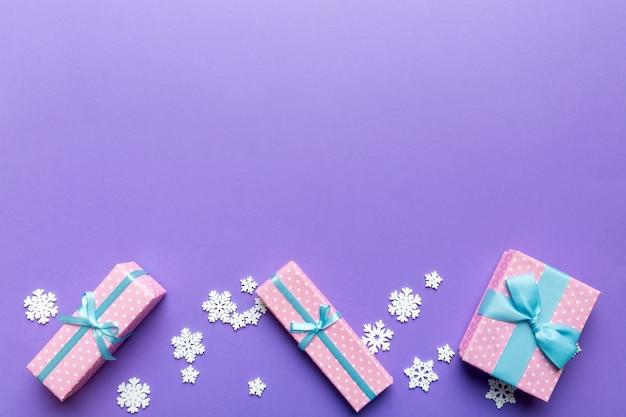 휴일 플랫은 다채로운 종이로 싸인 선물 상자와 함께 놓여 있고 색종이 조각으로 장식된 배경에 묶여 있습니다. 크리스마스, 생일, 발렌타인 및 판매 개념, 평면도.