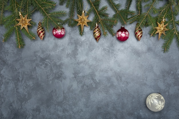 Holiday frame of christmas decorations on blue dark stucco concrete background with fir branch