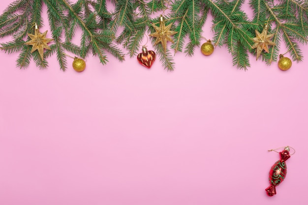 Holiday frame of christmas decorations on pink background with fir branch