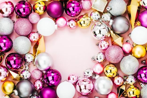Праздничная рамка из стильных рождественских блестящих безделушек и золотых кристаллов на пастельно-розовом фоне. плоская планировка, вид сверху