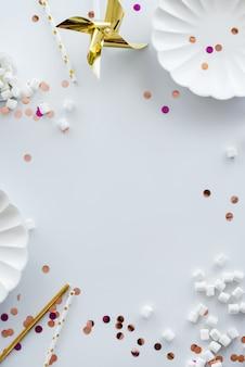 ホリデーフレームまたは背景にカラフルなキラキラ、紙吹雪、ゴールデンスター、マシュマロ、白いお皿、スティック。フラットレイアウトスタイル。コピースペースで誕生日やパーティーのグリーティングカード。