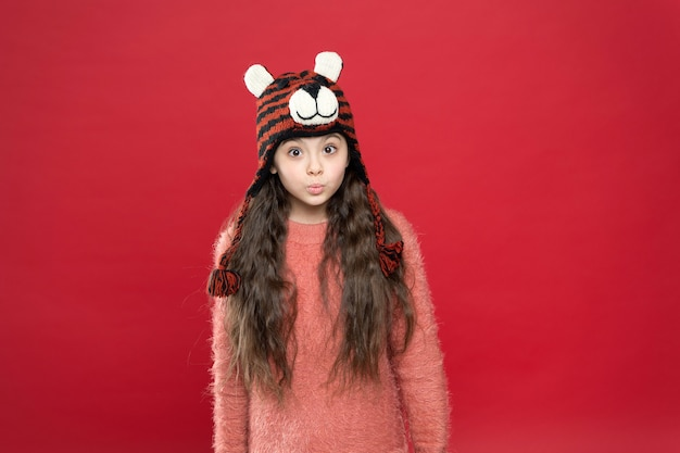 Holiday fun. cold season accessory. serious child in warm clothing. stylish teen girl with long hair in earflaps. winter kid fashion. happy childhood.